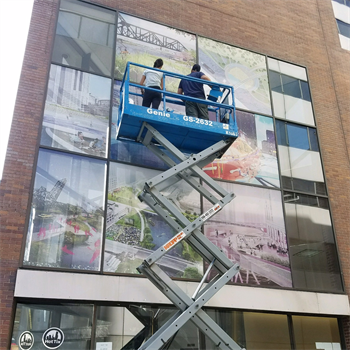 window decals being installed via workers on a crane
